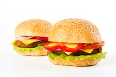 Two large burgers on a white background. Unhealthy food.  Royalty Free Stock Photography