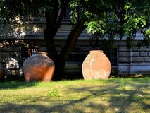 Two large ceramic antique vessels adorn the park near the ancient building. Summer day royalty free stock photography