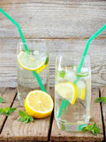 Two large glass of cold lemonade with ice, lemon, mint leaves Royalty Free Stock Images