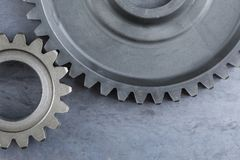Two Large Interlocking Gears on s Steel Sheet. A close up detail of two interlocking metal gears on a steel background Stock Image