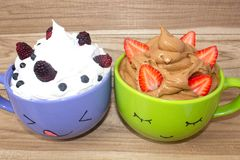 Two large mugs with painted faces, whipped cream and berries stand on a wooden shelf. Chocolate mousse with strawberries. And vanilla mousse with blackberries stock photo