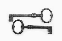 Two parallel keys on a white background. Two large old well-used iron keys lying parallel on a white background Stock Photo