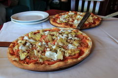 Two large pizzas and plates on table of restaurant Royalty Free Stock Photography