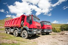 Two large red dump trucks. At construction site, in a sunny summer day Royalty Free Stock Image