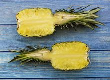 Two large ripe halves of pineapples over wooden background in tropical theme stock photo