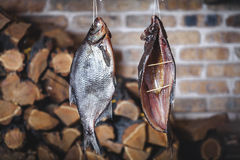 Two large smoked fish hang on background of stacked firewood Stock Image