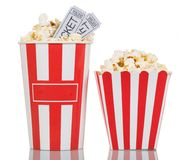 Two large striped boxes filled with popcorn, movie tickets on wh. Two large striped boxes filled with popcorn and movie tickets gray on a white background Royalty Free Stock Image