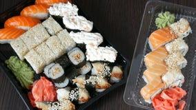 Two large sushi sets with lots of sushi, roll, maki, nigiri, gunkan. Stylish sushi sets on black wooden table. Two large sushi sets with lots of sushi, roll stock video footage