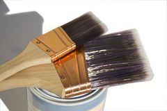 Three synthetic paint brushes. Two large synthetic high quality paint brushes sitting on a paint tin with a white isolated background Stock Photo