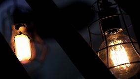 Two large vintage electric lights burn in the dark outside. In the yard lamps protected by a metal grate illuminate the courtyard at dusk. Outdoors in the stock video