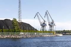 Two industrial cranes and coal piles. Two large white industrial cranes next to large coal piles Royalty Free Stock Photography