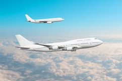 Two large white passenger airplanes fly parallel to each other in the sky above the clouds. royalty free stock image