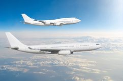 Two large white passenger airplanes fly parallel to each other in the sky above the clouds. stock photography