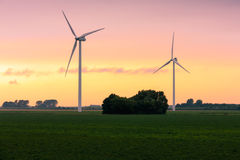 Two large wind turbines at sunset Royalty Free Stock Photo
