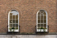 Two large windows with flowers. On a brick building Stock Image