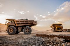 Two very large Mining Dump Trucks for transporting ore rocks. Two large yellow Dump Trucks transporting Platinum ore for processing at sunset in South Africa Stock Image