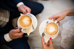 Two late art caffee cups. Couple of people holding cups with caffee with late art in the cafe Royalty Free Stock Image