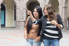 Two latin girls smiling and pointing a place Stock Photography