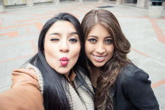 Two latin girls taking a selfie. Outdoors Stock Photography