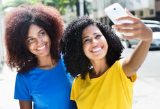 Two latin woman taking picture with phone Royalty Free Stock Photos
