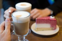 Two latte coffees with foam and cake woman and man Royalty Free Stock Image