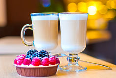 Two Lattes and raspberries with blackberries tart Royalty Free Stock Image