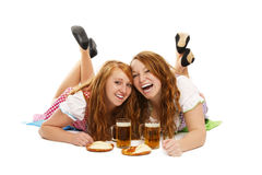 Two laughing bavarian girls with beer and pretzels. On the floor on white background Royalty Free Stock Photo