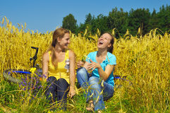 Two laughing beautiful girls rest in golden field. Two laughing beautiful girls rest in golden summer field Royalty Free Stock Photo
