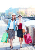 Two laughing beautiful girls with shopping bags and cup of coffe Stock Photo