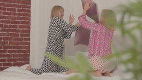 Two laughing blonde Caucasian friends fighting with pillows at the white bed. Beautiful girls having pajama party in the. Bedroom at home stock video footage