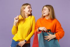 Two laughing blonde twins sisters girls in vivid clothes hold credit bank card, package bag with purchases after stock images