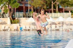 Two laughing boys jumping in outdoors swimming pool Royalty Free Stock Photo