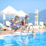 Two laughing boys jumping in outdoors swimming pool. Two happy children, twin brothers are jumping into swimming pool at the resort with mountains at the Royalty Free Stock Image
