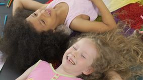 Two laughing children lying on floor and having fun, wonderful time being young. Stock footage stock footage