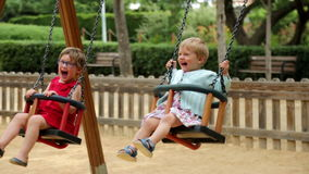 Two laughing children. On swing in summer park stock video footage