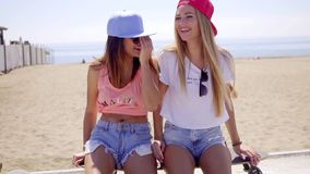 Two laughing friends in shorts sitting near beach stock video