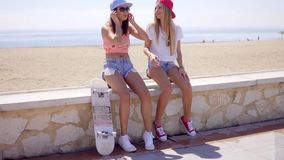 Two laughing friends in shorts sitting near beach stock video footage