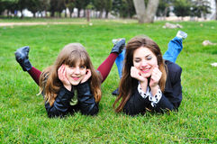 Two laughing girl. Two  laughing  teen girls laying on the green grass Royalty Free Stock Photos