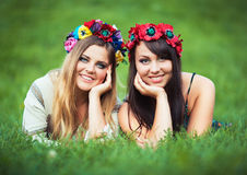 Two laughing girl in Ukrainian national costumes lie on the gree Royalty Free Stock Image