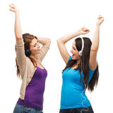 Two laughing girls with headphones dancing. Music and technology concept - two laughing teenagers with headphones dancing Stock Photo