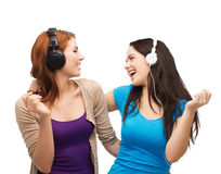 Two laughing girls with headphones. Music and technology concept - two laughing teenagers with headphones Royalty Free Stock Images