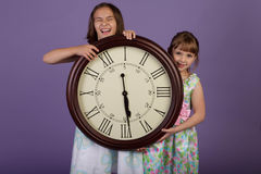 Two laughing girls holding a large wall clock Stock Image