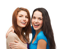 Two laughing girls hugging. Friendship and happy people concept - two laughing girls hugging Royalty Free Stock Photos