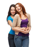 Two laughing girls hugging. Friendship and happy people concept - two laughing girls hugging Royalty Free Stock Photo