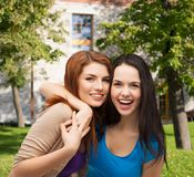 Two laughing girls hugging. Friendship and happy people concept - two laughing girls hugging Royalty Free Stock Image