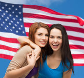 Two laughing girls hugging. Friendship and happy people concept - two laughing girls hugging over american flag background Royalty Free Stock Photo