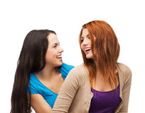 Two laughing girls looking at each other. Friendship and happy people concept - two laughing girls looking at each other Royalty Free Stock Photos