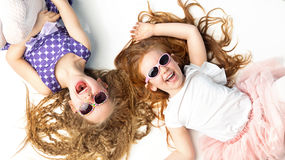 Two laughing girls lying on a white floor Stock Images
