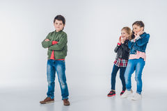 Two laughing girls making fun of boy standing with crossed arms. On grey Royalty Free Stock Images