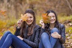 Two girls having fun in autumn park royalty free stock photo